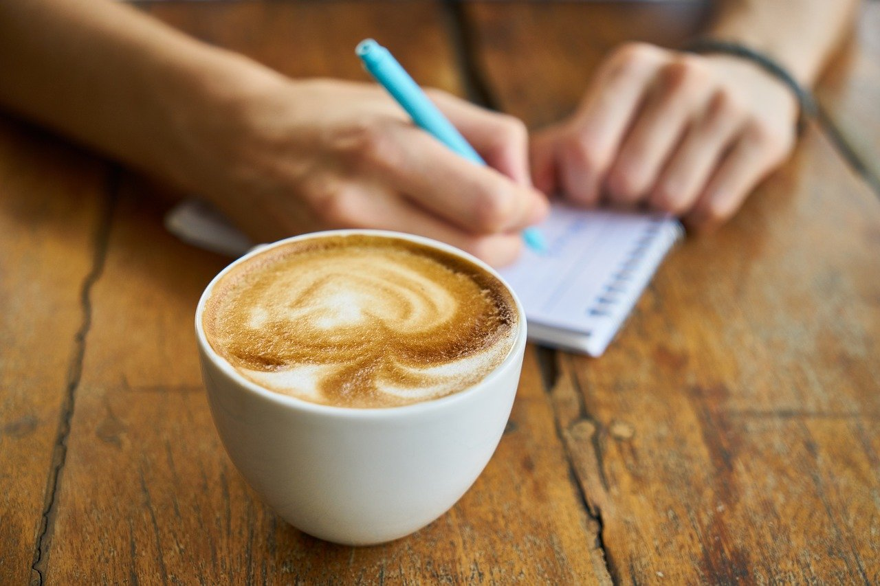 cappucino in a white cup on a wooden table with someone taking notes on a notepad in the background