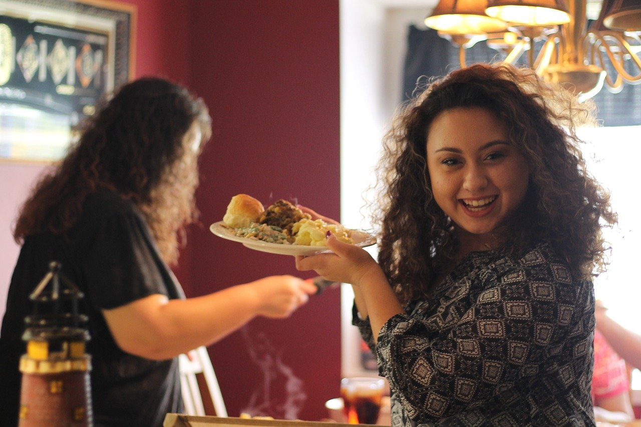 young woman with curly hair getting her plate of food at a family gathering