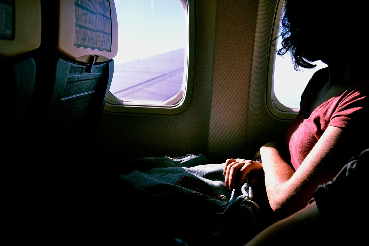 woman sitting on airplane staring out of her window