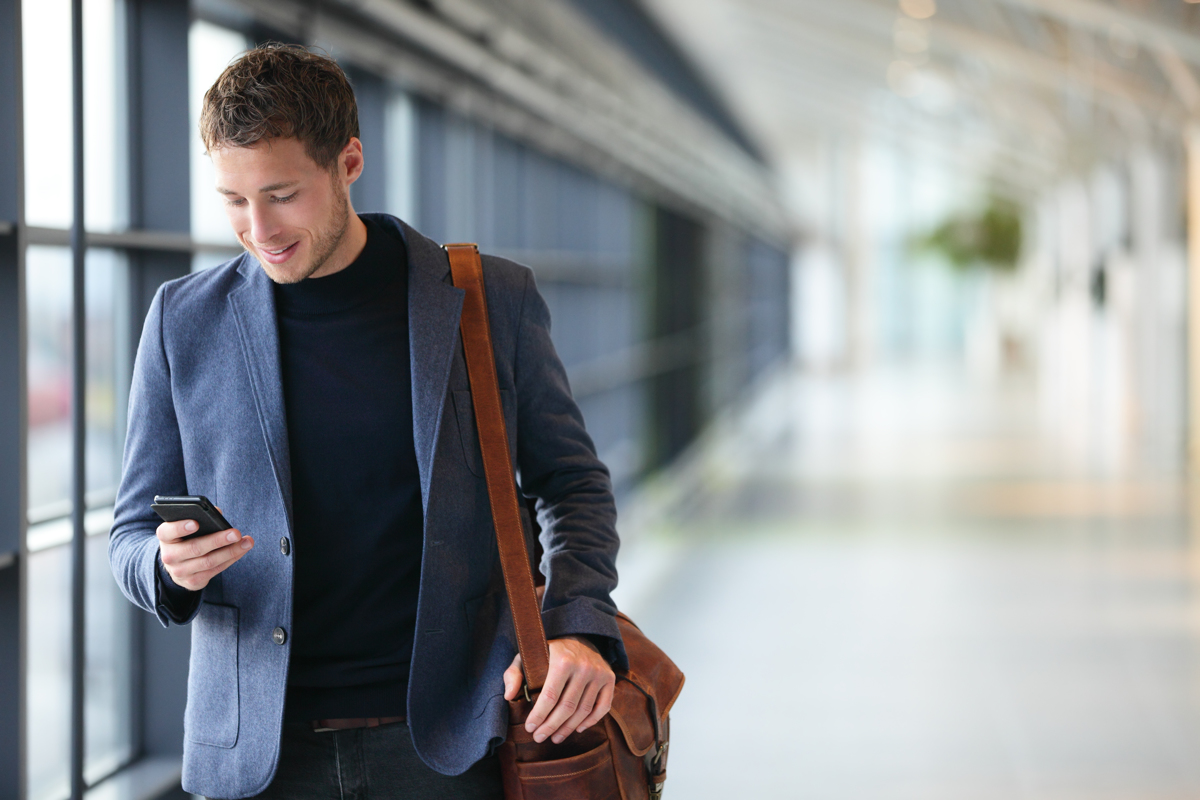 young business man walking through the airport looking at his smart phone and carrying his luggage over his shoulder