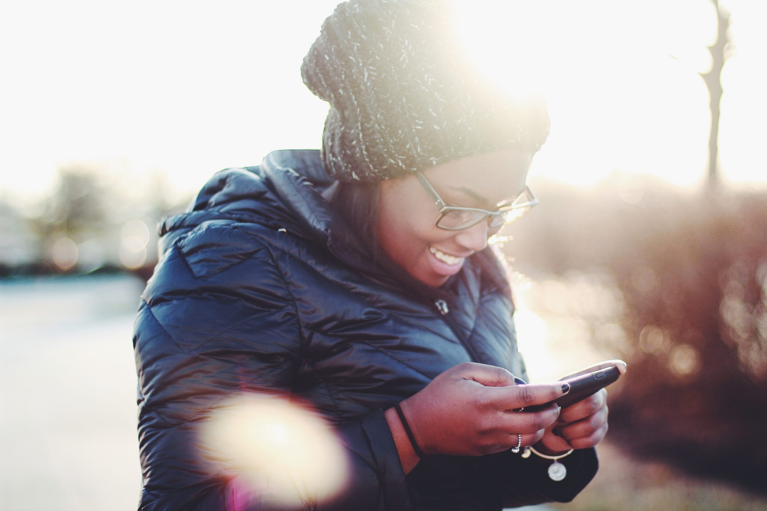 young woman smiling and looking down at her cellphone