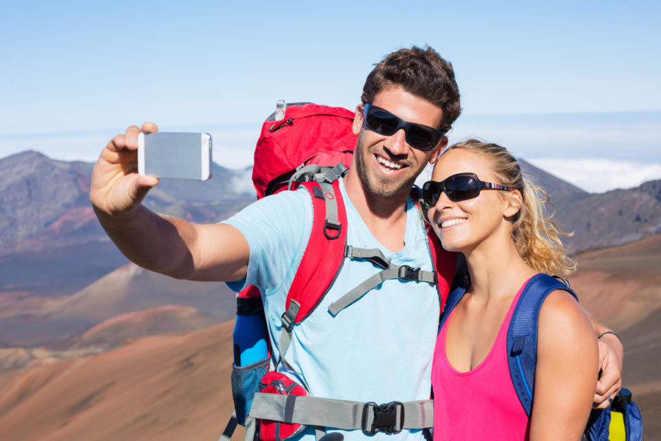 """Happy couple taking photo of themselves with smart phone outdoors, Taking a """"selfie"""""""