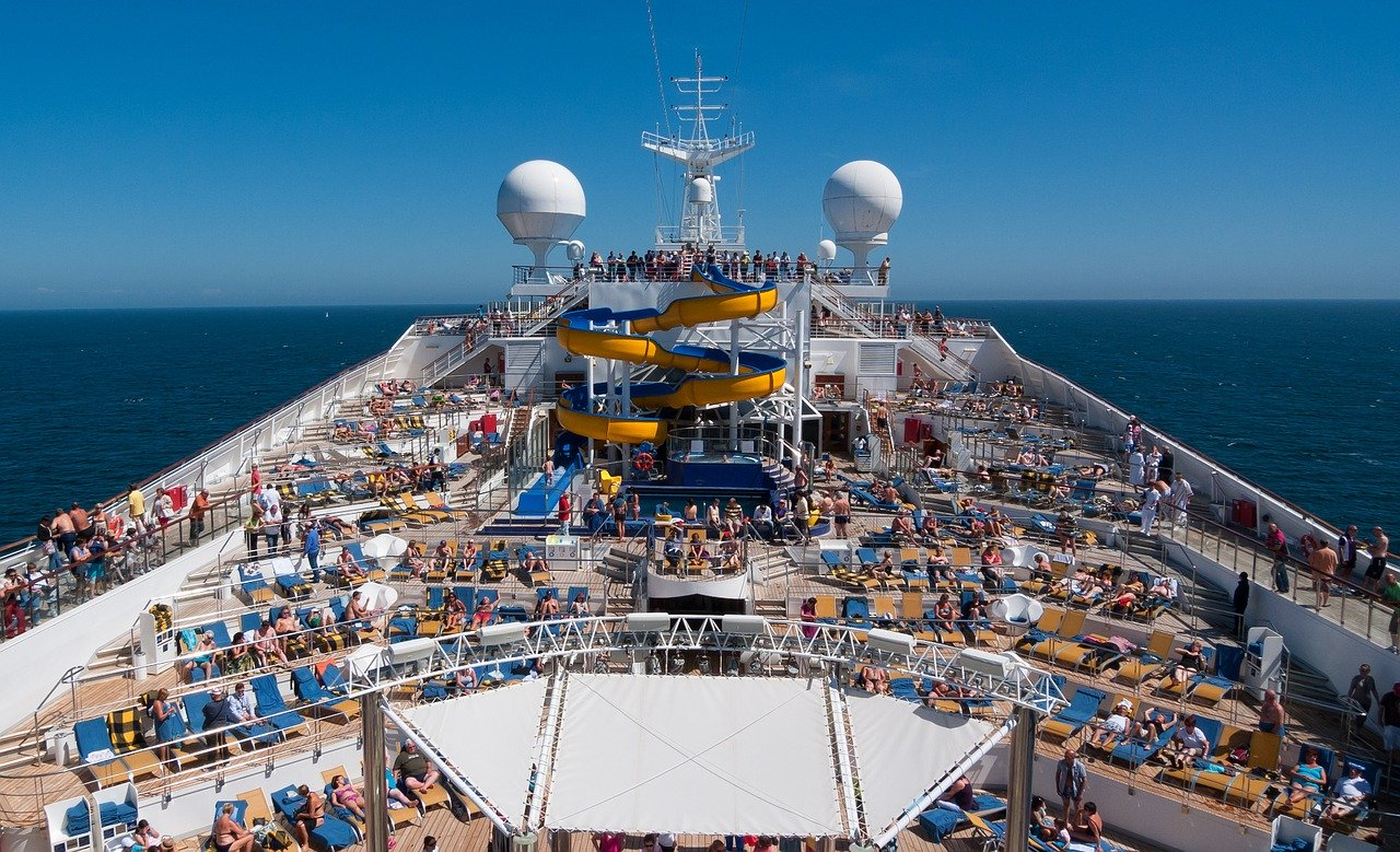 top view of a cruiseship with many people at the pool and a water slide
