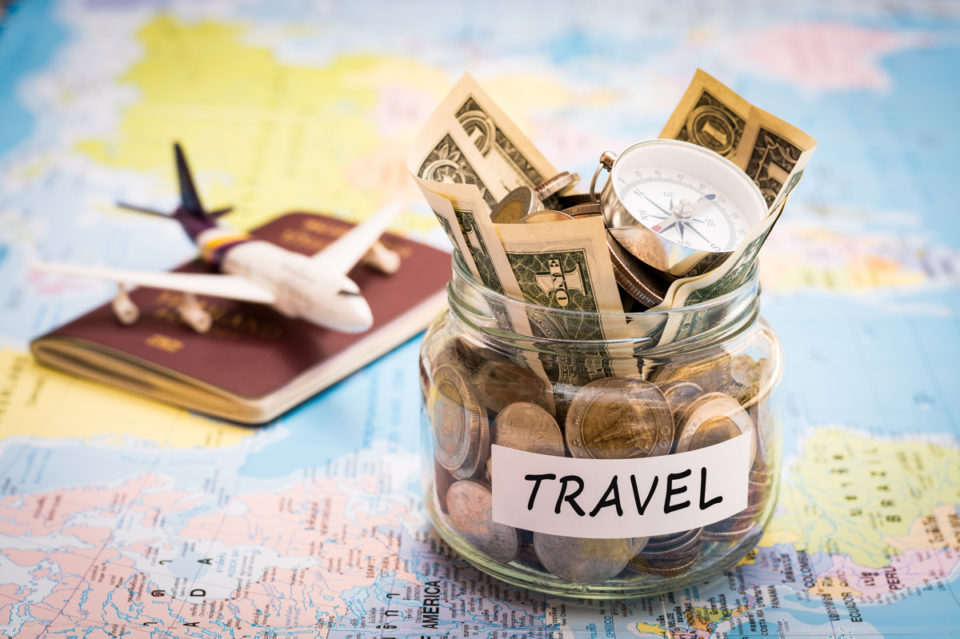 Travel budget concept. Travel money savings in a glass jar with compass passport and aircraft toy on world map