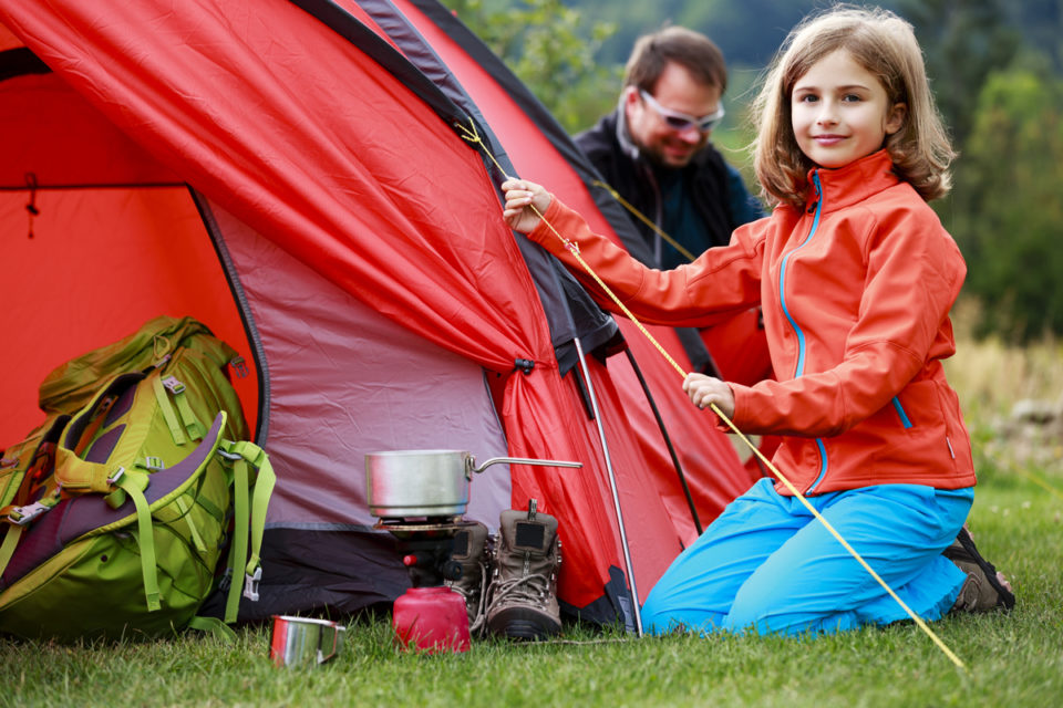 Camp in the tent - family setting a tent on the camping