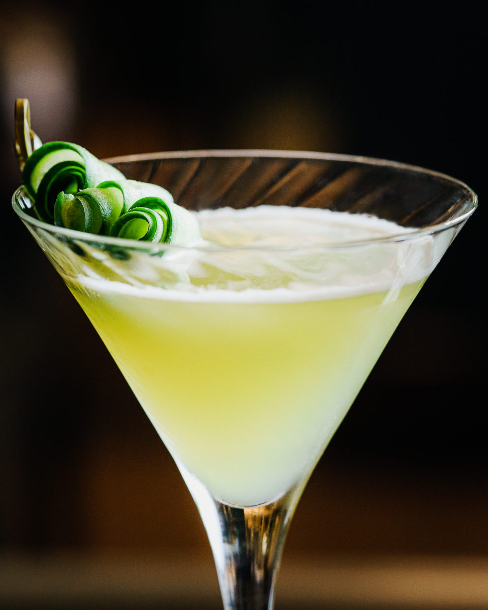 a yellow margarita with green garnish in a glass
