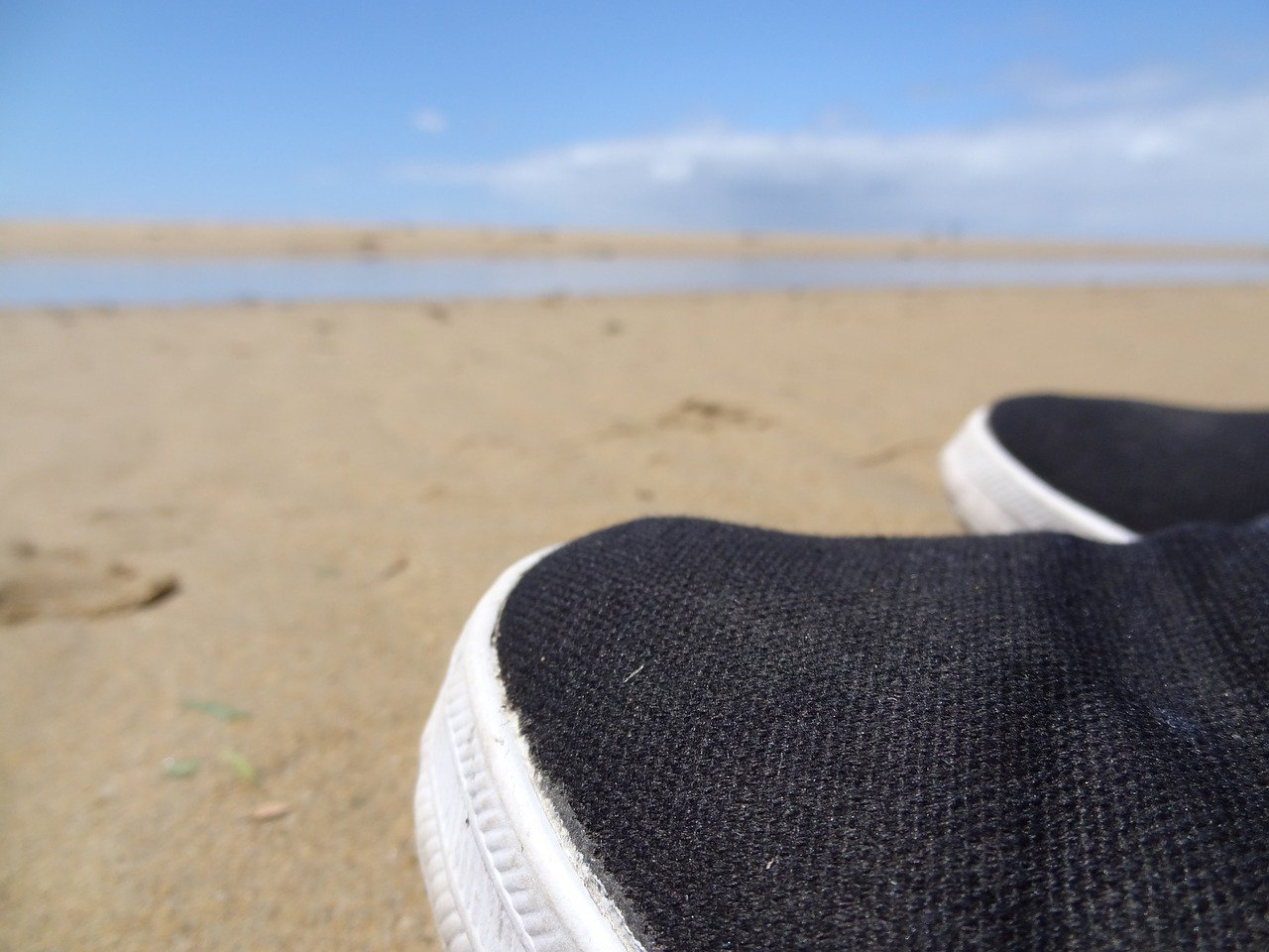 close up of black and white water shoes on the beach