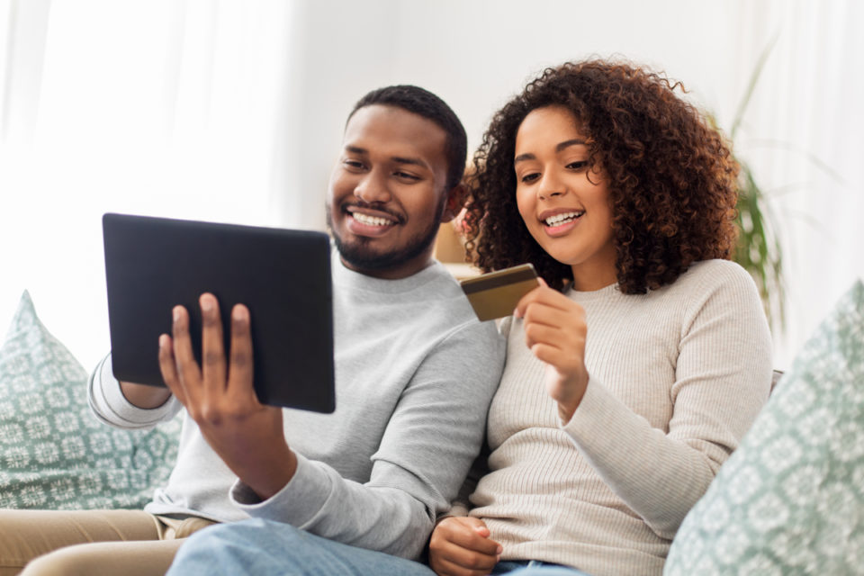 happy couple couple with tablet pc computer and credit card at home