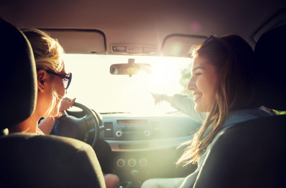 happy teenage girls or young women driving in car