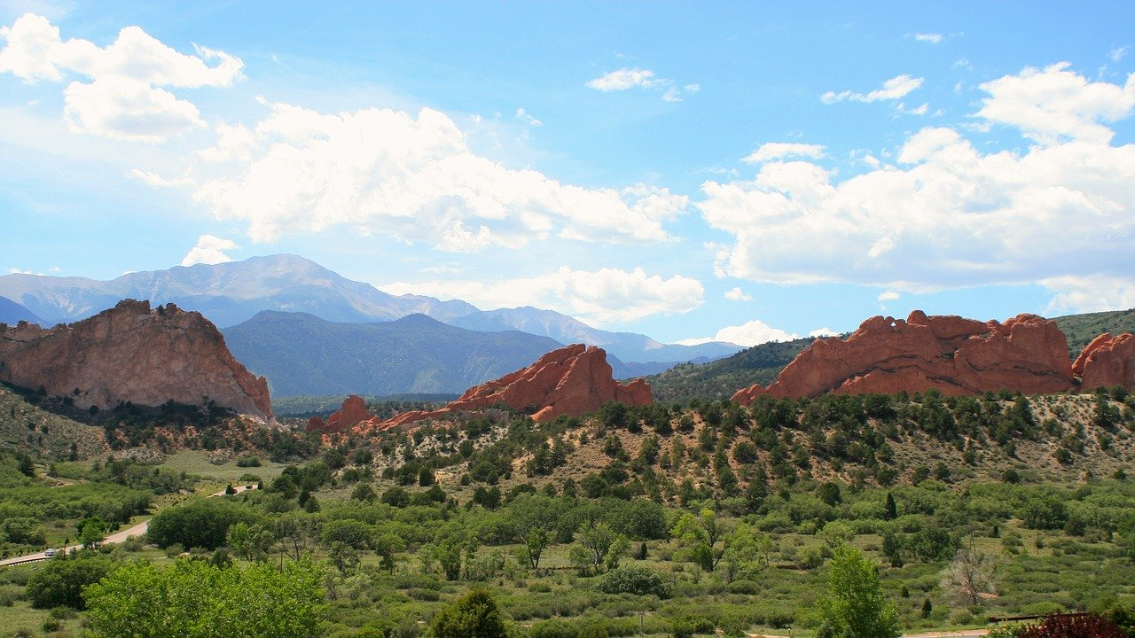 Colorado Springs with blue skies, greenery and mountains in the background
