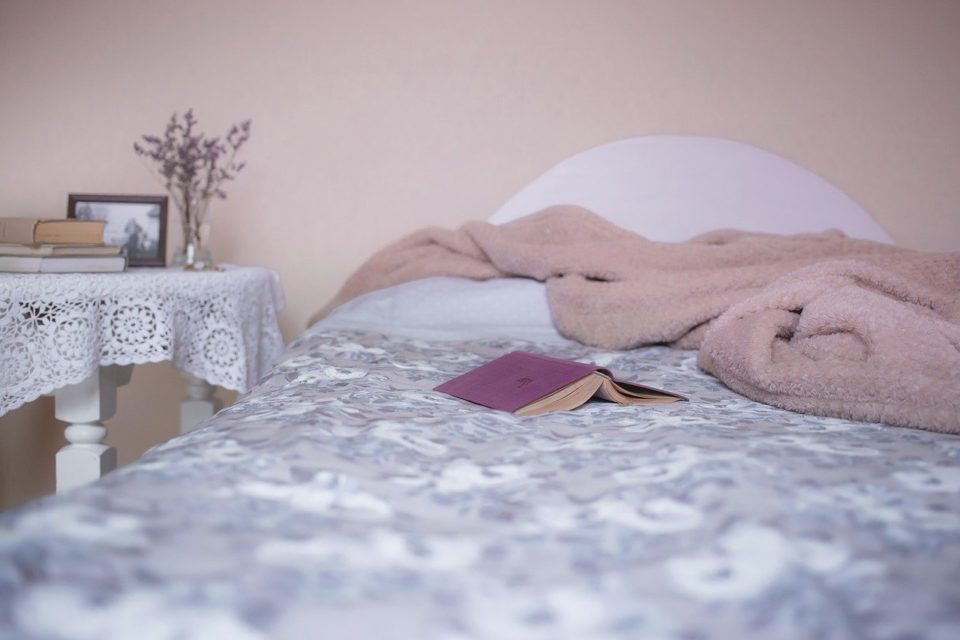 purple book on a cozy bed, comfortable setting, relaxation concept