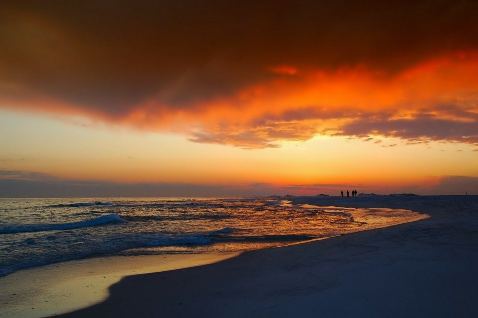 orange sunset setting over a secluded Florida beach